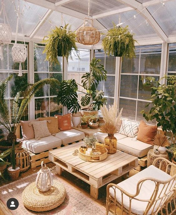 a beautiful boho sunroom with a pallet sectional sofa, a pallet table, a rattan chair, potted plants all over, pendant lamps and a jute pouf