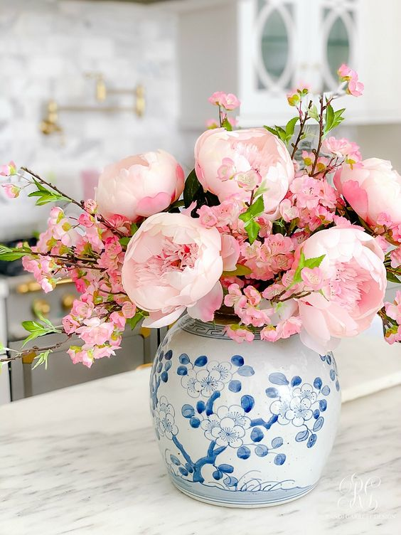 a blue floral vase with pink peonies and cherry blossom is a beautiful spring decor idea for a preppy space