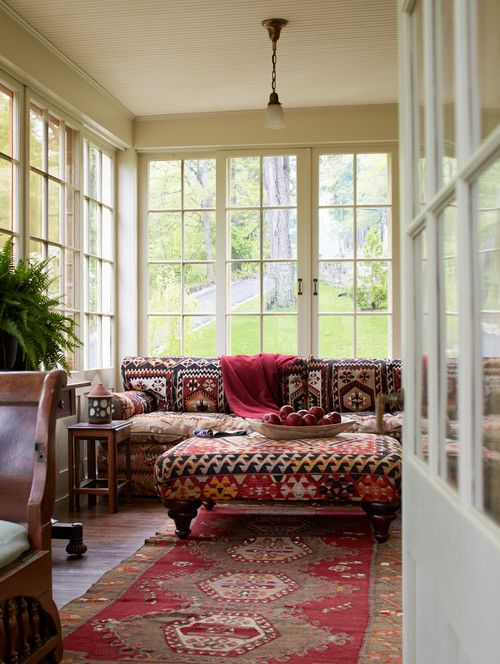 a bold boho sunroom with a red printed boho sofa, a matching ottoman, a red printed rug, rich-stained furniture and potted greenery