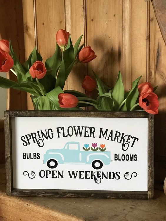 a bright and fun spring sign with a pastel truck and blooms and letters in a simple stained wooden frame