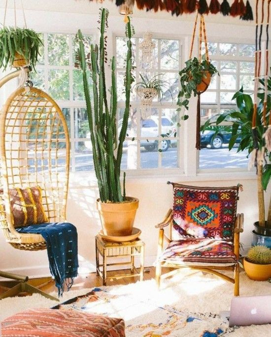 a bright boho sunroom space with a wicker pendant chair, a colorful chair, layered rugs, potted plants and a view