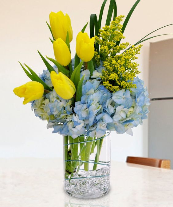a bright spring flower arrangement with yellow tulips and mimosa plus blue hydrangeas is a bold statement
