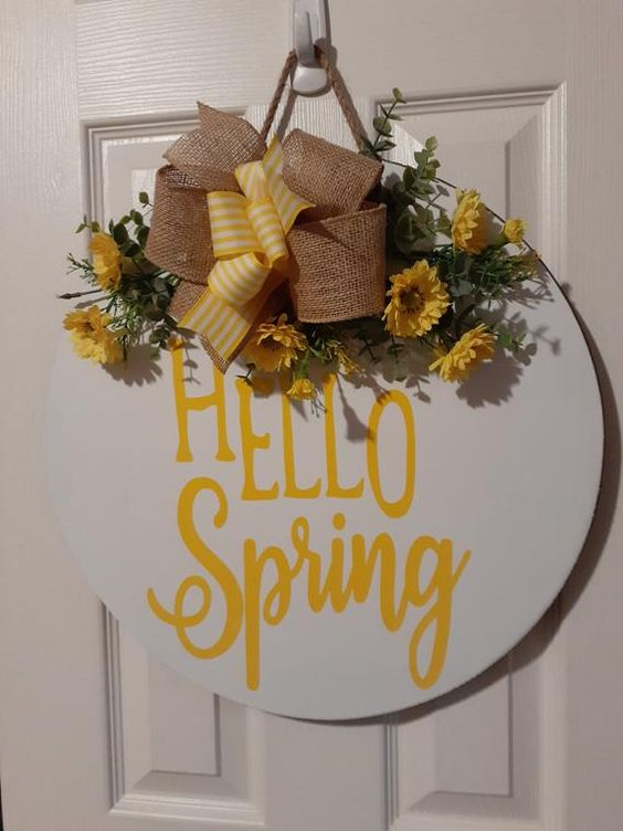 a bright spring sign with a striped and burlap bow, bright yellow blooms and greenery and yellow letters