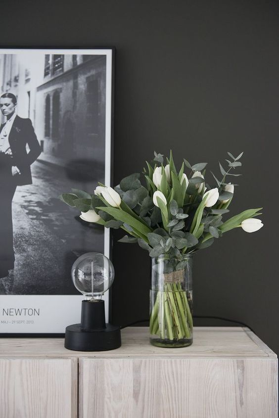 a chic and stylish spring flower arrangement of white tulips and eucalyptus in a clear vase is very modern