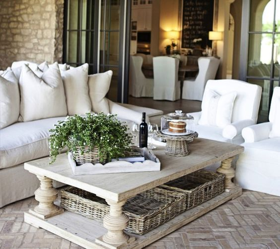 a chic farmhouse coffee table with basket trays under it to store some blankets, pillows and stuff like that