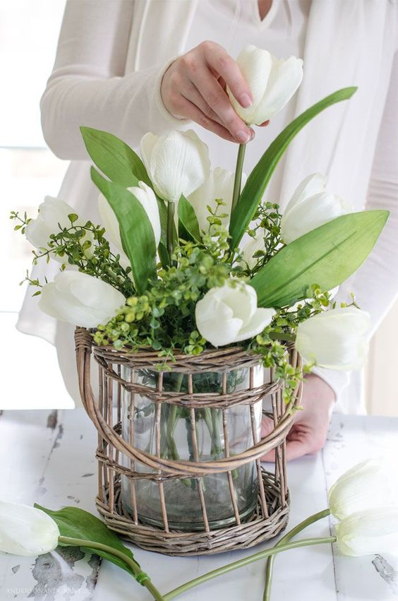 a clear vase with green hydrangeas and white tulips placed in a wicker holder is a lovely spring decoration in rustic style