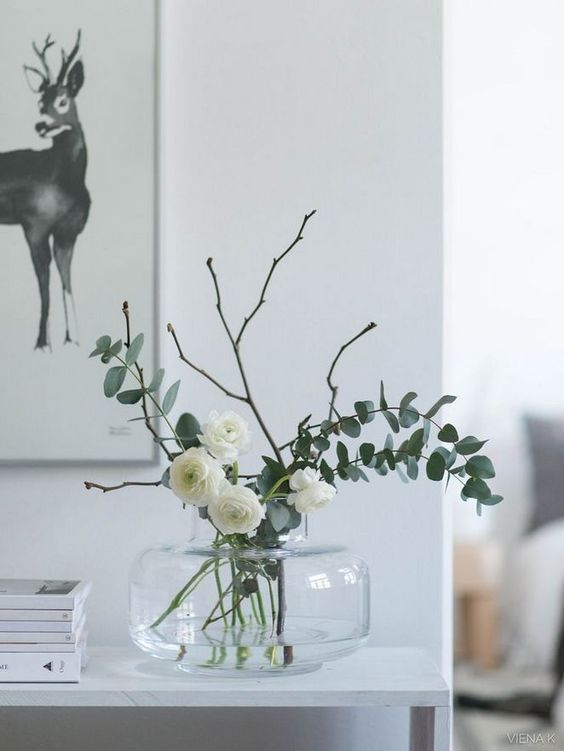 a clear vase with white ranunculus and eucalyptus and twigs is a lovely and fresh spring idea