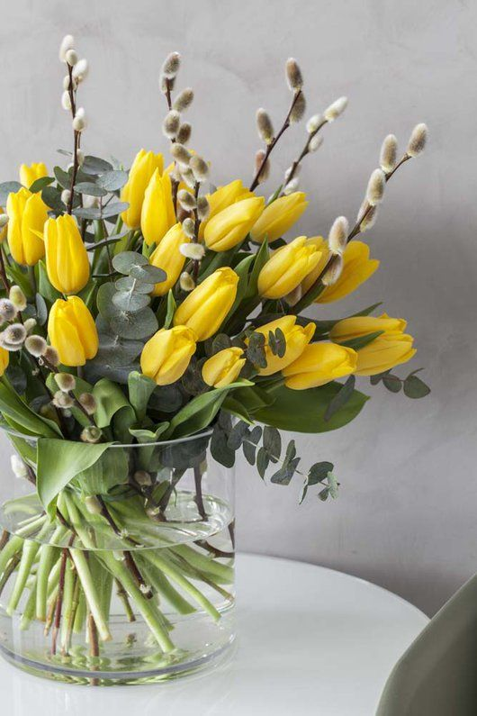 a clear vase with yellow tulips and willow plus a bit of eucalyptus is a lovely and bold spring flower arrangement