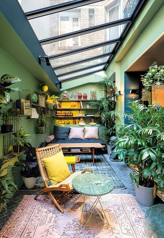 a colorful sunroom with green walls, bright furniture, potted greenery and blooms