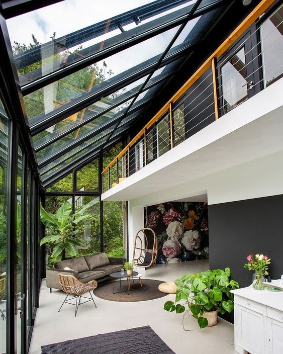 a contemporary sunroom with stylish modern furniture, potted greenery and rugs and lots of sunshine