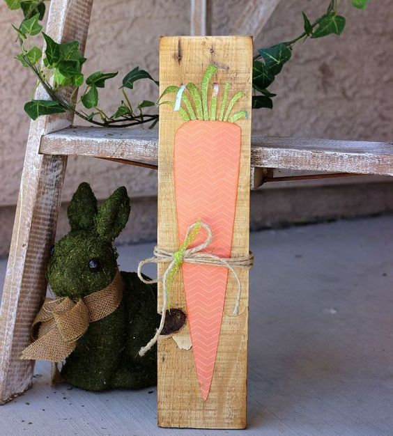 a cute and simple carrot pallet sign with dimension and a twine bow is a lovely idea for spring