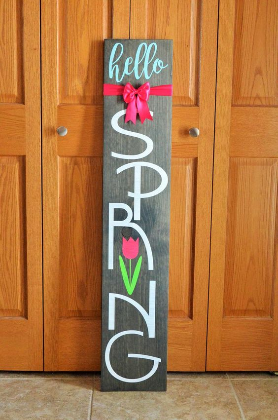 a dark stained wooden sign with a pink bow and a pink tulip is a lovely idea for outdoors