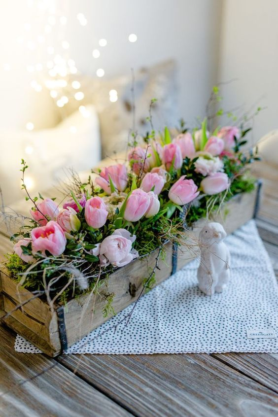 a fabulous rustic arrangement of a wooden box, moss, greenery, pink tulips and some twigs is very fresh and cool