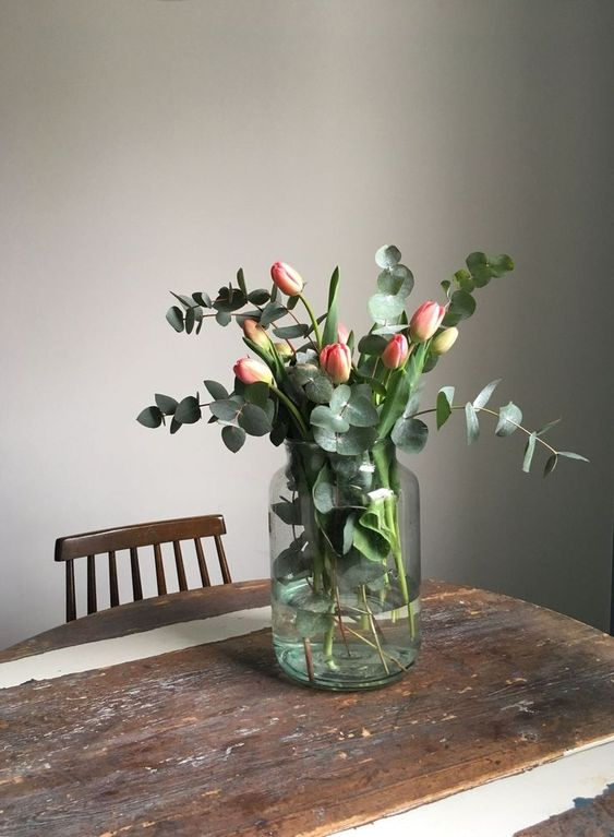 a large jar with pink tulips and fresh eucalyptus is a very lovely and cool spring flower arrangement you'll enjoy