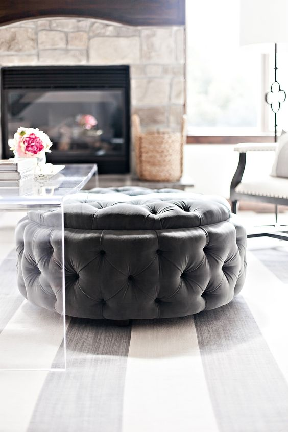 a large round tufted ottoman can be placed under the coffee table and you can store stuff inside it