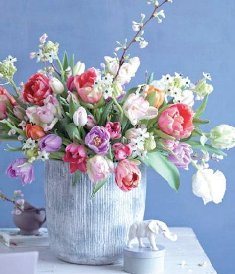 a large vase with colorful tulips and some white blooms is a gorgeous spring-inspired floral arrangement