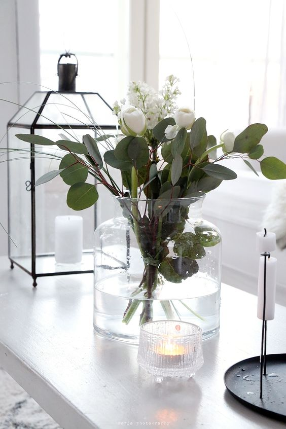 a large white vase with white blooms and eucalyptus is a classic flower arrangement that always works