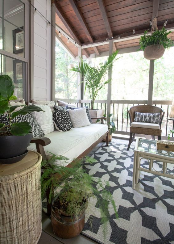 a lovely boho sunroom with a printed rug and pillows, a white sofa, wicker chairs and a rattan table plus potted greenery