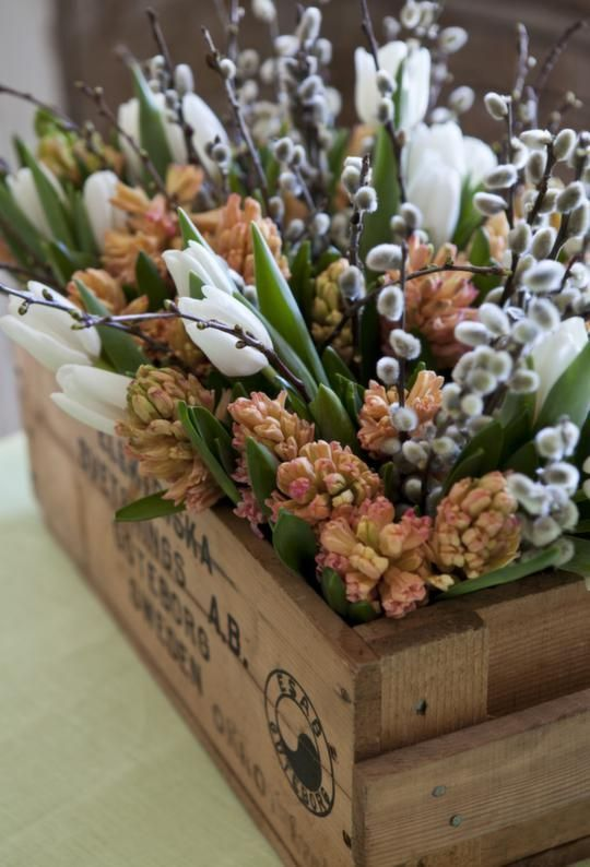 a lovely rustic spring floral arrangement of a wooden box, rust tulips, white ones, willow and leaves is amazing