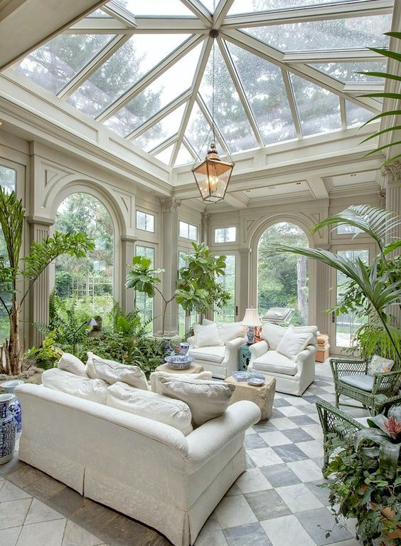 a lush sunroom or orangery with neutral furniture, tan poufs, a pendant lamp and lots of potted greneery and blooms