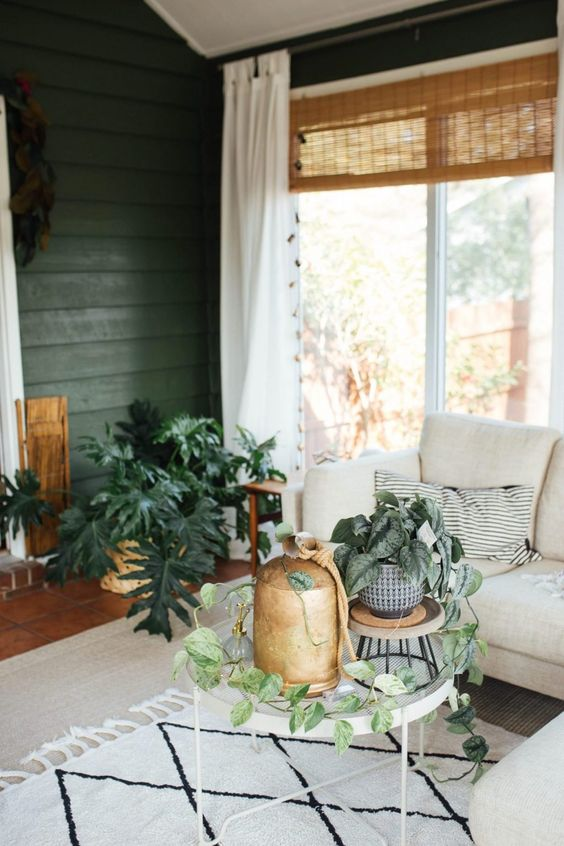 a mid-century modern boho sunroom with green walls, a neutral sectional, round tables, potted plants and woven shades
