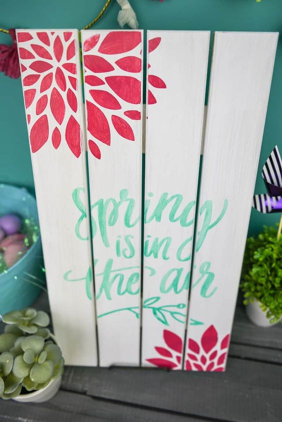 a painted wooden spring sign with green letters and red blooms is easy to make and very bright