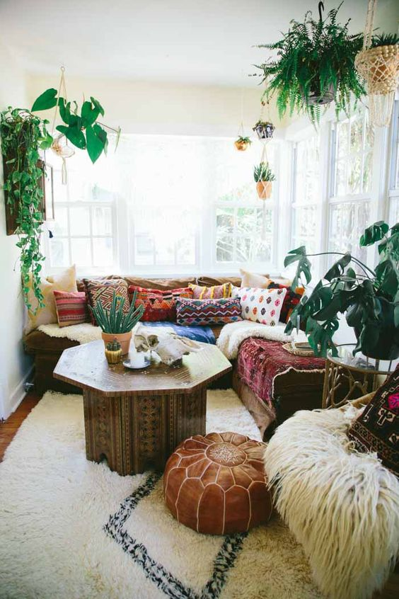 a pretty and bright boho sunroom with a sectional, colorful pillows and blankets, a carved wooden table, a leather pouf and potted plants