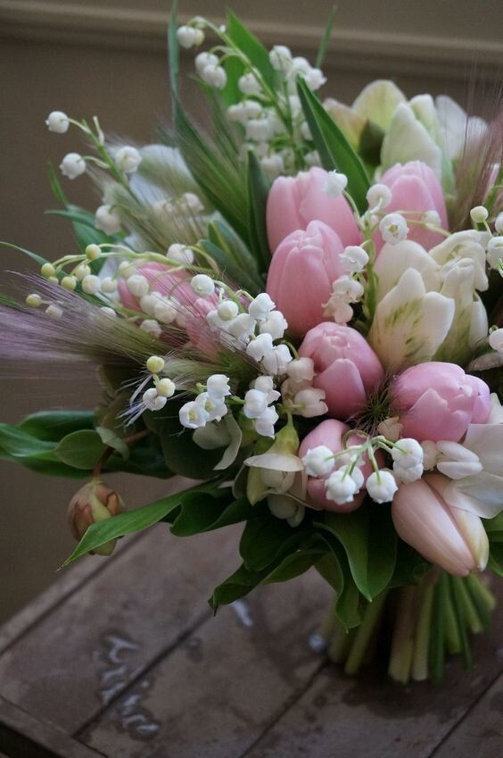 a pretty floral arrangemnt with pink and white tulips, lily of the valley, some grass and leaves is amazing for spring