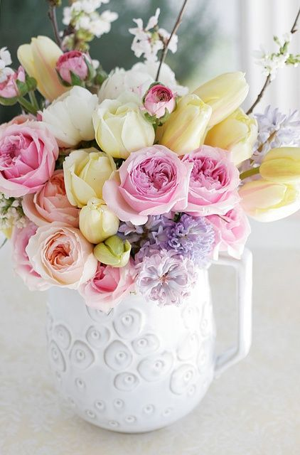 a pretty jug with yellow tulips, pink and peachy peony roses, cherry blossom and purple blooms is a bright spring arrangement