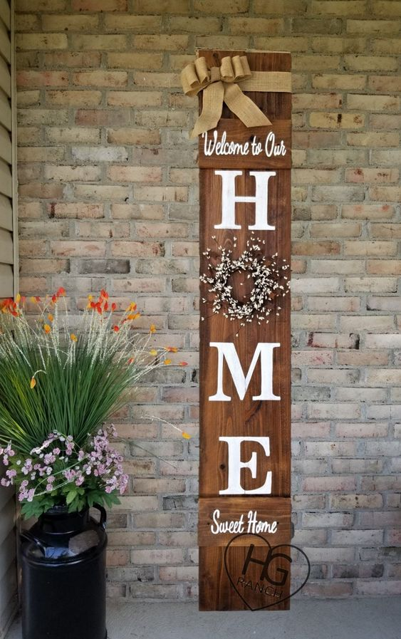 a rustic spring sign of a stained piece of wood, with a blooming wreath, a burlap ribbon and some letters