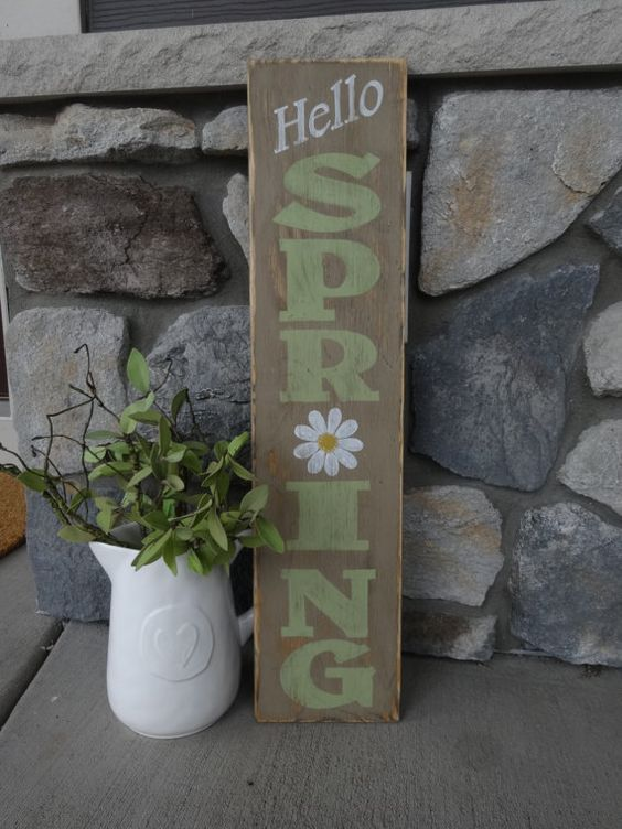a rustic spring sign with green letters, a white bloom is a simple and easy idea for a rustic outdoor space