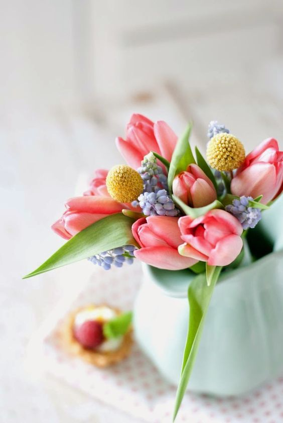 a simple and beautiful spring flower arrangement with blue, yellow and pink blooms and leaves is a chic idea