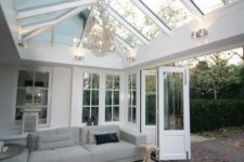 a simple and contemporary sunroom with a large grey sectional, a black ottoman, a vintage chandelier and folding doors