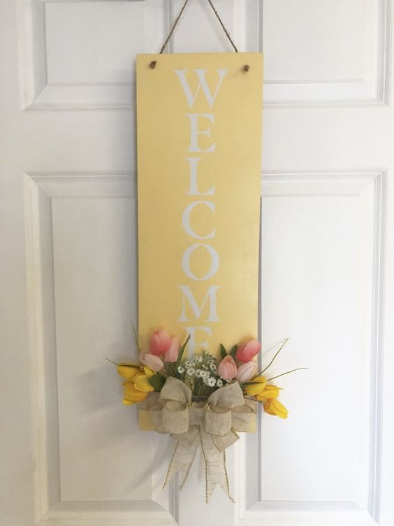 a simple yellow sign with pink and yellow blooms, greenery and a burlap bow will substitute a usual door wreath