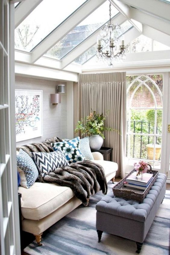 a small refined sunroom with elegant furniture, lots of pillows, a fir throw, a vintage chandelier and neutral curtains