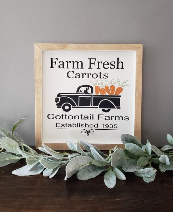 a small spring sign with a truck carrying carrots, with some letters and in a simple wooden frame