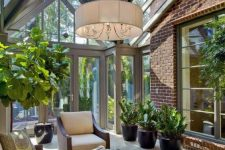 a stylish mid-century modern sunroom with elegant dark furniture, potted greenery, a pdant lamp and much light