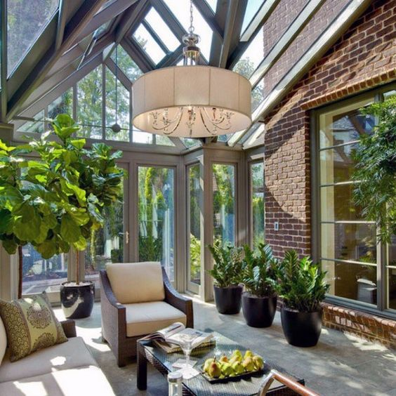 a stylish mid century modern sunroom with elegant dark furniture, potted greenery, a pdant lamp and much light