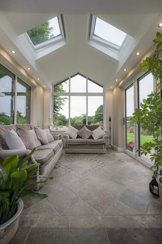 a stylish modern sunroom with elegant sofas, potted greenery and nice views is welcoming