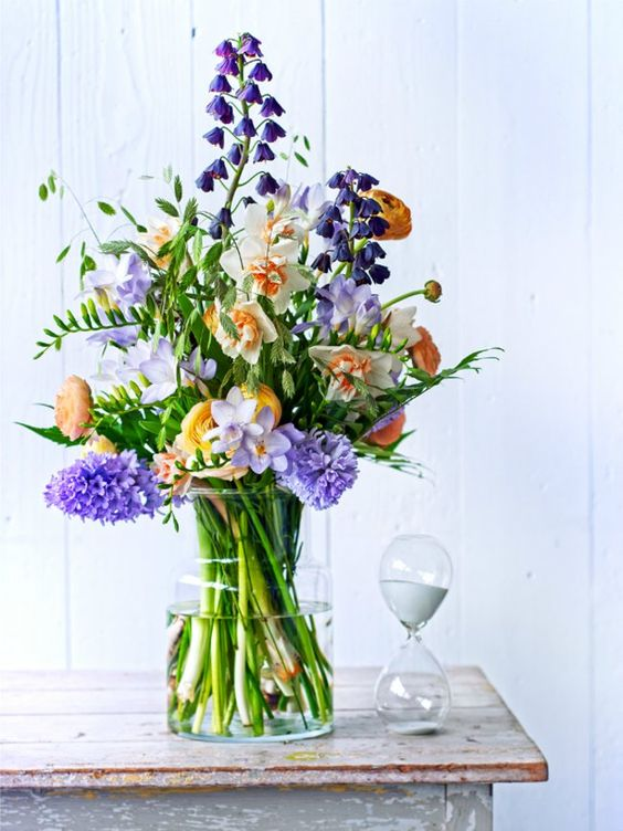 a super bright flower arrangement in purple, rust, yellow and peachy plus greenery is a bold spring decor idea