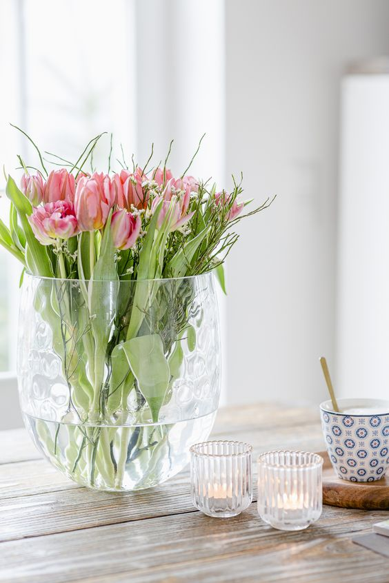 a tall vase with lots of pink tulips and willow is a fresh and easy spring flower arrangement to make yourself