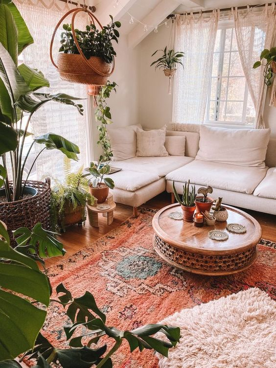 a very cozy boho sunroom with a white sectional, a wooden carved table, lots of potted greenery, layered rugs and macrame curtains