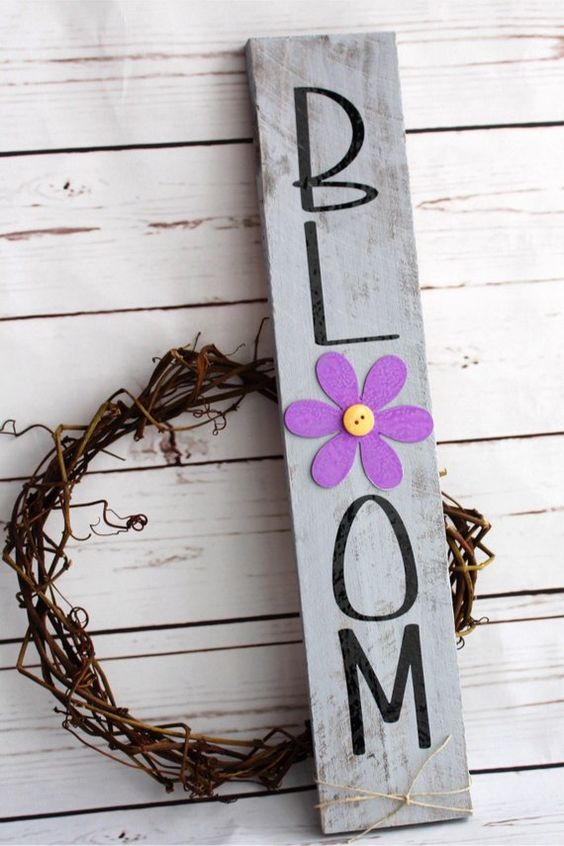 a vine wreath paired wiht a grey rustic sign with a bold purple bloom and black letters is a lovely idea