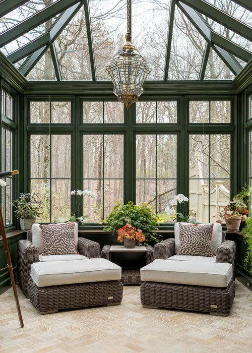 a vintage sunroom with dark rattan furniture, potted plants and blooms and a vintage pendant lamp