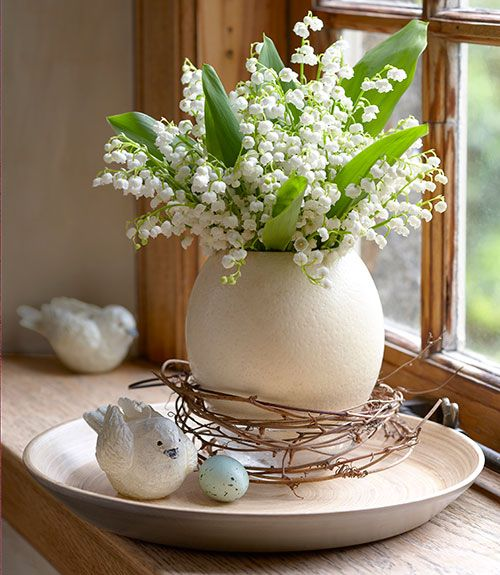 a white porcelain vase with lily of the valley is a lovely spring arrangement with a gorgeous aroma at the same time