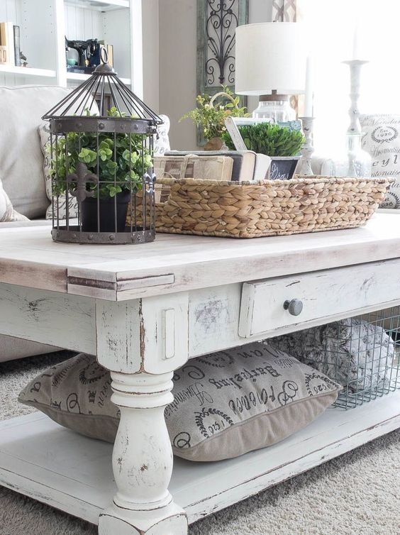 a white shabby chic coffee table with a wire basket and a pillw that are stored under the tabletop