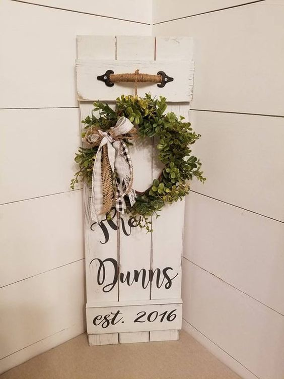 a white sign with a greenery wreath, burlap and plaid bows, a twine handle is a chic idea for a rustic space