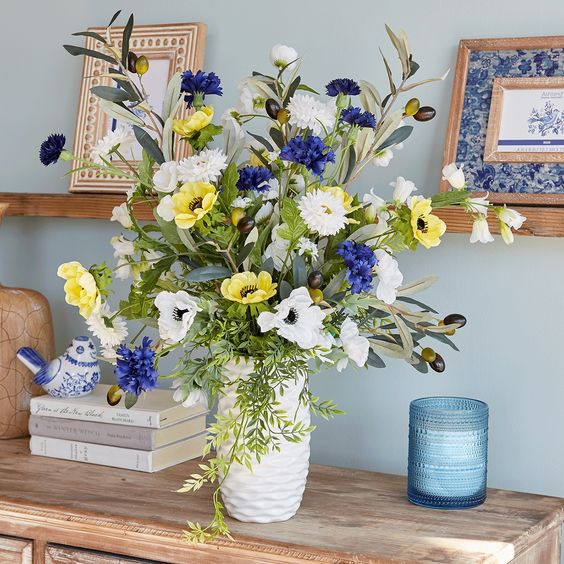 a white textural vase with white, purple and yellow blooms and olive branches with olives is a non-typical idea