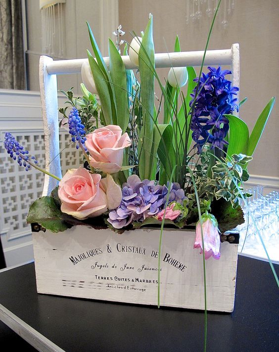 a white toolbox with purple hyacinths, pink roses, white tulips and some greenery is a beautiful and chic decoration