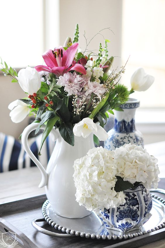 a white vase with pink, blush and white blooms, greenery and twigs of various kinds for a spring rustic space